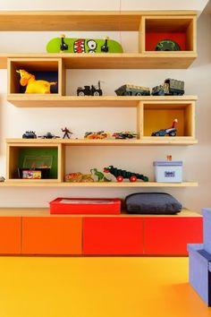 Na brinquedoteca nessa casa espaçosa tem gavetas setorizadas por cores, mesa de atividades, suportes para bolas de futebol e uma estante de ponta a ponta