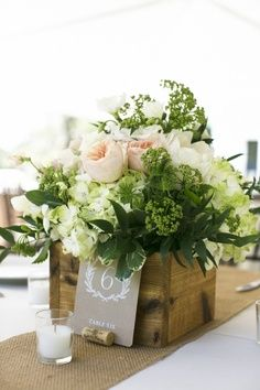 Some tables will have a square wood box spilling with seasonal greenery, white hydrangea, and blush spray roses. Surrounded by mercury glass votives.