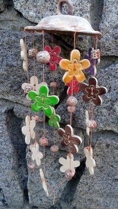 Keramická zvonkohra kytičková s vrchlíkem Na vrchlíku obarveném oxidem železa, jsou zavěšeny tónované barevné kytky a zdobené kuličky. Na zavěšení jsem použila oranžovou voskovanou šňůru. Vše je ze světlé keramické hlíny. Hodí se do dětského pokoje, na terasu, do zahrady... Krásně cinká. Délka i s vrchlíkem je 40cm Šířka vrchlíku je 14cm.