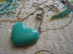 Colar em metal na cor prata com pingente de coração de resina verde água.    Altura regulável. R$29,90