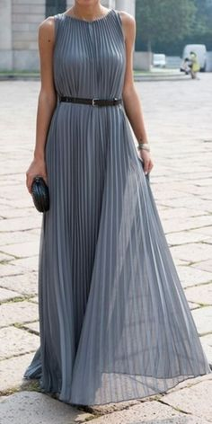 Elegant grey pleated sleeveless maxi dress with black leather belt and black leather clutch and shoes