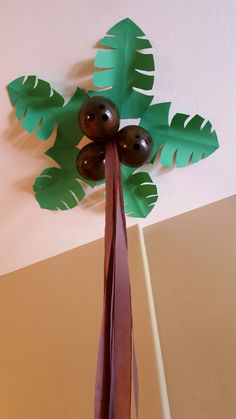 I ordered the biggest available green construction paper from amazon. First made rounded diamond (simple leaf shape) then made the palm slits. Brown balloons, and we have high ceilings, I measured 8 ft. 10 strands a tree trunk. It takes time however super cheap and very impressive!
