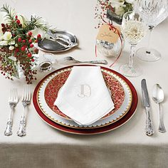 Set a Distinctive Christmas Table | Mix traditional and modern: Monogrammed linens, crystal stemware, and silver flatware establish a classic tone. Bold red chargers and graphic gold-trimmed china update the display