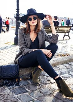 Polienne Riemis wears a camisole, blazer, skinny jeans, ankle boots, round sunglasses, a saddle bag, and a wide-brim hat