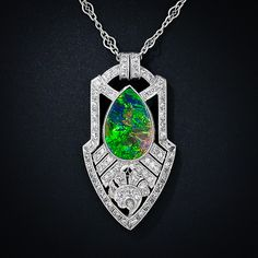 A mesmerizing and gemmy Lightening Ridge black opal is elegantly and artfully presented in a consummate Art Deco pendant necklace, finely hand crafted at the peak of Art Deco period - circa 1925. The fabulous pear shape opal displays an electric and iridescent kaleidoscope of predominantly blue, green and orange hues with a splash of red. The striking and sophisticated platinum and diamond setting is signed Walton & Co