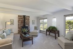 The family room features a gorgeous view with large windows spanning the wall and gives an inviting, vintage feel with the iron stove.