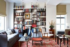 Loft living space with a wall of books, a gray sofa, and a Persian area rug