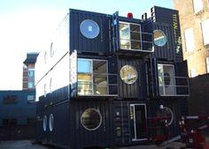 Edifici construït amb contenidors i obertures redones.