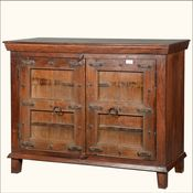 """This rustic buffet will take you back to a simpler time. This 51"""" long sideboard is decorated with double Gothic inspired doors complete with iron brackets and studs, window pane style framing, and classic ring pulls.  The simple cabinet frame stands on short legs. The handmade buffet is constructed with solid reclaimed hard wood. The wood surface and metal details are original and have been seasoned by time. The cabinet doors open onto a large cupboard space with two shelves."""