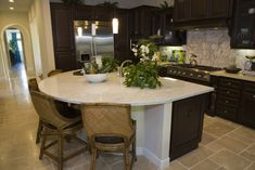 Dark wood high end kitchen with rounded island and light counter color