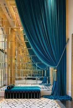 Stunning teal drappery with mirored wall and cushion carpet..blue giving royal and classy touch and gold a neo emphase