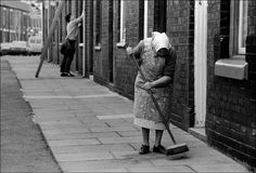 ian berry(1934- ), g.b. england. lancashire. blackburn. old woman sweeping paving stones in front of her terraced house with a window cleaner in the background. http://pro.magnumphotos.com/Asset/-2S5RYD5IWD8.html