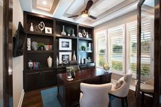 This home office, designed by Mary DeWalt Designs, provides a strong, masculine aesthetic as your eye feasts on the rich, dark woods of the desk, bookcase and flooring. DeWalt employed just a touch of blue in the area rug to reflect the color scheme she used for the rest of the home.
