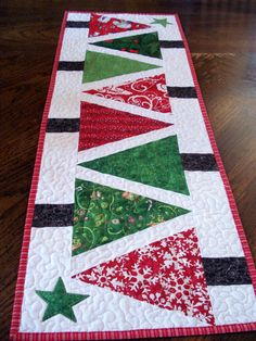 Quilted Table Runner Modern Christmas Trees, narrow runner red and green patchwork, bright and festive runner for your home decor  This 12 x 34 inch runner is a fun and modern style featuring trees in bright christmas fabrics. I accented the straight piecing with fun curves and loops for the quilting. The batting is Warm and Natural cotton blend, so there will be some shrinkage when washed, you can dry flat instead of in the dryer to minimize this effect. This quilt would also look great…