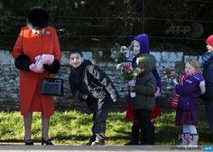 UNITED KINGDOM, SANDRINGHAM : Children queue to give gifts and flowers to Britain's Queen Elizabeth II (L) following a traditional Christmas Day Church Service at Sandringham in eastern England, on December 25, 2013. AFP PHOTO / ADRIAN DENNIS