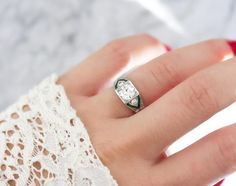 The Roxanne ring is an Art Deco engagement ring circa 1930 centering a 1.02 carat old European cut diamond with emerald accents in a platinum setting!