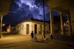 On a summer night, in the colonial town of Santa Clara, Cuba, people hurry to get home before the storm.