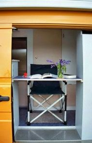 small fold down table in campervan door - ideal fresh air workspace. just like a mini balcony