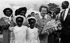 British Prime Minister Margaret Thatcher poses with two young girls after they presented her with a bouquet of flowers.
