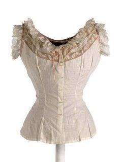 """Cubrecorsé realizado en batista de algodón, es ajustado, sin mangas y con escote redondo. Remata con una puntilla de encaje mecánico que se prolonga en la sisa y un pasacinta de seda que termina en los hombros en una lazada, como en el delantero. En el lado inferior derecho, bordado: """"P R"""". 1890-1902 (ca)"""
