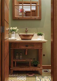 Adaptado como bancada no lavabo, o aparador antigo ganhou tampo de mármore e cuba feita de tacho de cobre. Os metais (Deca) receberam um banho de cobre (Máster Acabamentos). No piso, os ladrilhos hidráulicos (Ceramik) compõem um patchwork.