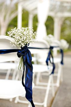 """Pew markers"" included tied bouquets of baby's breath attached to the chairs with navy ribbon. 