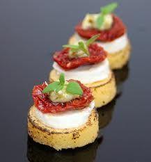 Siempre deliciosa... capresa de tomate seco, mozzarella y hierbas sobre una ruedita de pan