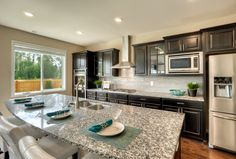 Simple place settings on the huge breakfast bar built in the Carnation floorplan in Lidera community in Bothell WA