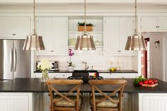 Hutker Architects    White beadboard kitchen cabinets & kitchen island, soapstone countertops, Visual Comforts Chart House Collection Sloane Single Shop Lights, soapstone farmhouse sink and French cafe barstools.