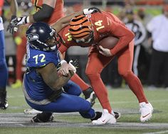 NFC defensive end Michael Bennett (72), of the Seattle Seahawks, sacks AFC quarterback Andy Dalton (14), of the Cincinnati Bengals, during the first half of the NFL Pro Bowl football game Sunday, Jan. 29, 2017, in Orlando, Fla. (AP Photo/Phelan M Ebenhack).