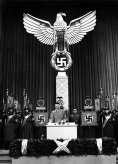 Adolf Hitler gives a speech to NSDAP members at an annual Party event. Behind him is a rare example of the German Imperial Eagle with a design differing from most of it's counterparts seen in the Reich.