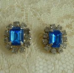 These earrings have large, 7 mm x 5 mm central rectangular-cut blue rhinestones, surrounded by 11 sparkling clear rhinestones, all prong set. The earrings measure a petite 1/2 x 7/16 inch. They are rh