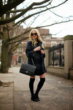 Black long blouse with dark blue and dark gey stripes warm long coat and shining black leather hand bag and black long socks and stylish bla...