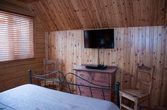 L'intérieur du Chalet le Malard. Chambre des maîtres, télé HD et DVD | lattes en pin, meuble, commode bois de rose, antique, chaise en bois, lumière, fenêtre, jour, stores horizontaux, chaleur
