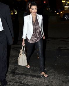 During a night out in NYC, Kim Kardashian donned a white blazer, metallic cowl top, black leather pants, a beige Hermes bag, then finished her look via black flip-flops instead of her usual edgy platform sandals.