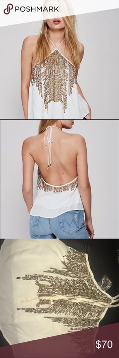 "Free people ""Smoke Screen Tank Top"" OUT OF STOCK New without tags flowy halter top with tie closure at the neck and low dipping back for a sultry silhouette. Eye-catching embellishments and sparkling sequins cascade from the neckline around to the back. Still has extra sequenced bag attached in case any falls off. Offers welcome  Shell: 100% Viscose Lining: 65% Viscose, 35% Cotton Bust: 36.5"" = 92.71 cm Length: 18"" = 45.72 cm Free People Tops"