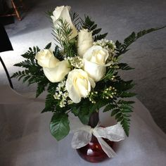 A more simplistic arrangement, this beautiful and aromatic collection of white roses, wax-flower, and some leather leaf is elegant. The red case with white bow completes this beautiful arrangement.