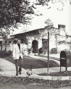 Cary Grant walking his Siamese cat in Beverly Hills by Sanford Roth, c. 1955.