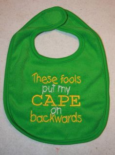 Cape bib in green with yellow and white writing by KenaKreations, $7.00