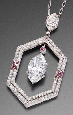 RUBY AND DIAMOND PENDANT, CIRCA 1925. Of hexagonal shape, set with diamonds and accented by two crossed ribbons set with calibré rubies, centring a 3.66 carat marquise cut diamond, surmounted by a square cut ruby, with French assay marks, signed Fillon Orfèvre Joaillier, 26 rue Montaigne Paris, the cover monogrammed F.L.M.
