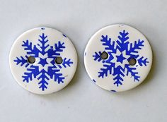 Handmade decorative polymer clay buttons with white background and pretty blue snowflakes . Add these sweet little buttons to your hand sewn, knit