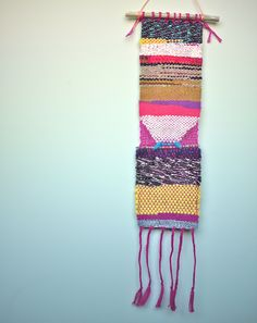 """Made on a vintage miniature loom, this handwoven wall hanging measures 4.5"""" x 21"""" (which includes the 6"""" fringe). The weaving is tied to a piece of driftwood from the Oregon coast. It is ready to hang."""
