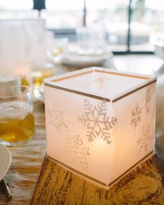 DIY Waxed Paper Snowflake Lantern | photos by Wynn Myers | Camille Styles •1 roll waxed paper •ruler •scissors •white acrylic paint •snowflake stencils •sponge brush •spray adhesive •5.5-inch wooden sticks