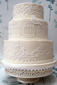 All white layered wedding cake with fondant birds and birdcages