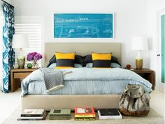 Bold and playful bedroom with yellow and blue hues, a night table with purple flowers, blueprint art above headboard and books at the foot of the bed