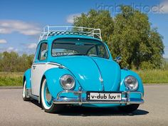AUT 23 RK2078 01 - 1970 VW Beetle Sedan Turquoise And White 3/4 Front View On Pavement By Grass And Trees - Kimballstock