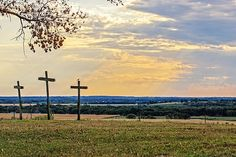 A mocking bird sits atop the cross on the right, like the thief that mocked Jesus. Taken atop Pork Chop hill near Baldwin City Kansas giving a vista of a sunburst over the Kansas countryside.