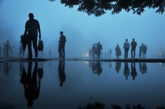 Pedestrians are reflected in a puddle after a rainfall in the northern hill town