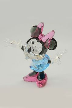 Minnie Mouse Eye-catching and colorful, Minnie strikes a playful and dynamic pose; She shines in Black Diamond crystal with a clear crystal face and gloves; Her eyes and nose gleam in Jet crystal and she wears a cute Aquamarine crystal dress and Rose crystal shoes; A must-have for Disney collectors! Diamond #Gloves #DressHome #HomeAccessories