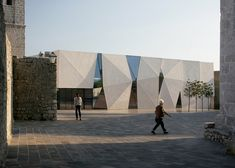 Concrete-clad sports hall by Idis Turato features both faceted and bumpy facades
